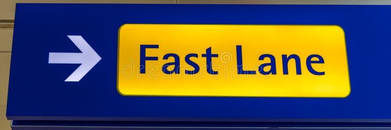 A faixa r?pida assina dentro azul e amarelo no fim do aeroporto acima Notificação luxuosa da primeira classe do aeroporto do sina fotografia de stock royalty free