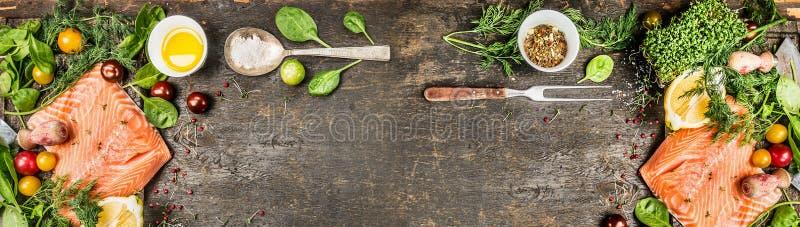 Faixa salmon crua com cozimento de ingredientes: lubrifique, tempero, colher e forquilha frescos no fundo de madeira rústico, vis fotografia de stock royalty free