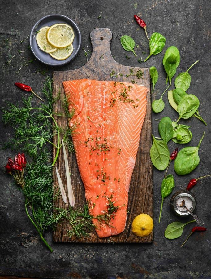 Faixa salmon perfeita na placa de corte rústica com os ingredientes frescos para o cozimento saboroso