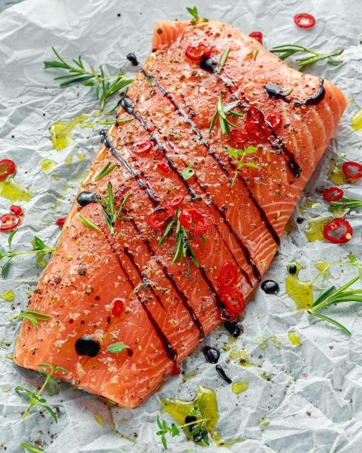 Faixa Salmon temperado em cozinhar o papel com sal do mar, pimenta, vinagre balsâmico, pimentões e alecrins Apronte para cozinhar imagem de stock
