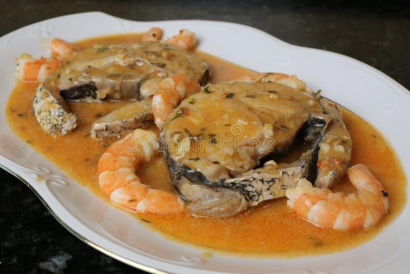 Faixas das pescadas no molho dos camarões um prato de peixes imagem de stock