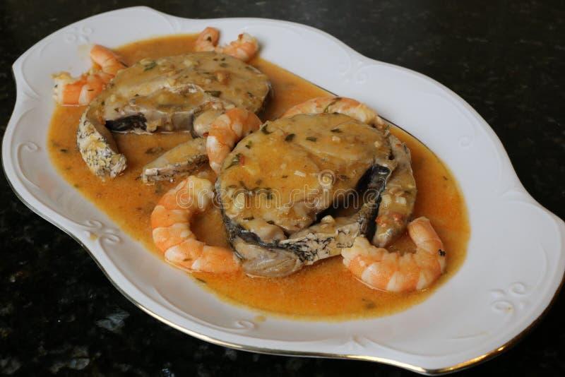 Faixas das pescadas no molho dos camarões um prato de peixes foto de stock royalty free