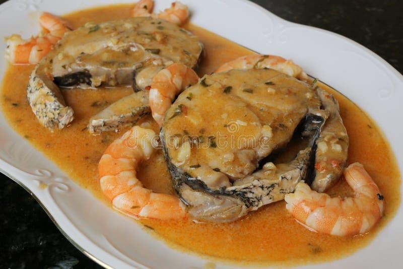 Faixas das pescadas no molho dos camarões um prato de peixes imagens de stock royalty free