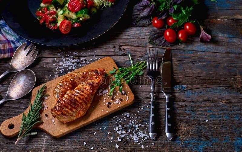 Faixas grelhadas da galinha na placa de corte de madeira imagem de stock royalty free