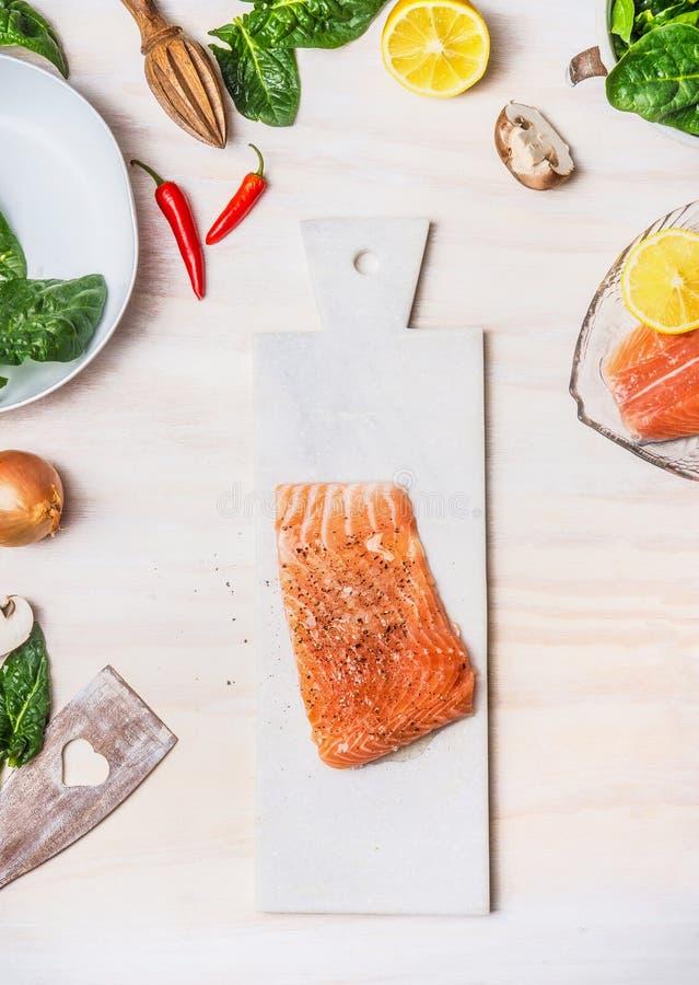 Faixas Salmon cruas na placa de corte branca com os ingredientes saudáveis no fundo da mesa de cozinha, vista superior imagem de stock royalty free