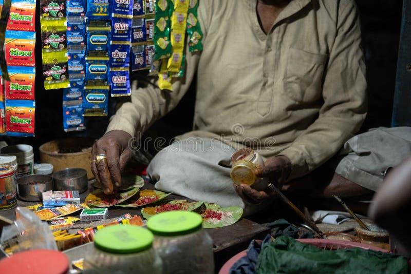 A man prepares a popular digestif called paan. Faizabad, Uttar Pradesh / India - April 4, 2019: A man prepares a popular digestif called paan stock photo