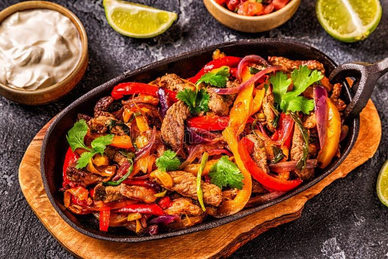 FAJITAS с покрашенным перцем и луками, который служат с tortillas стоковое фото