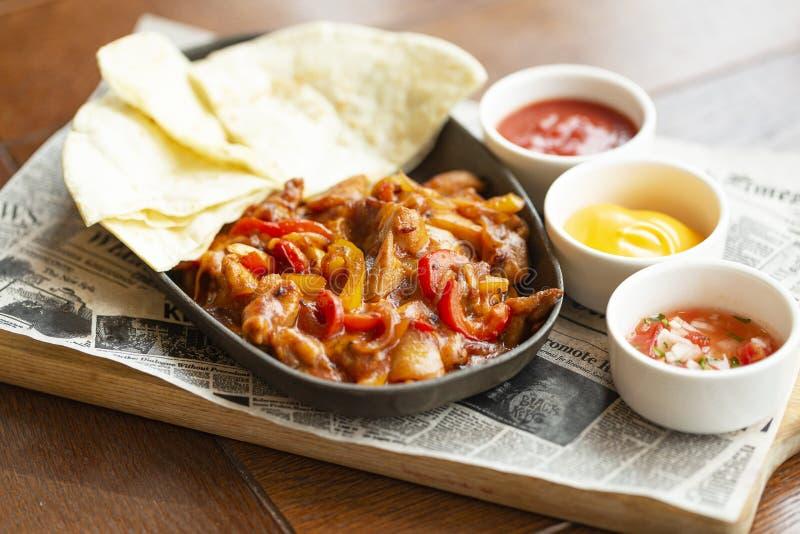 Fajitas da carne com as cebolas e a pimenta colorida, servidas com tortilhas, molho de queijo, salsa e creme de leite Prato tradi imagens de stock