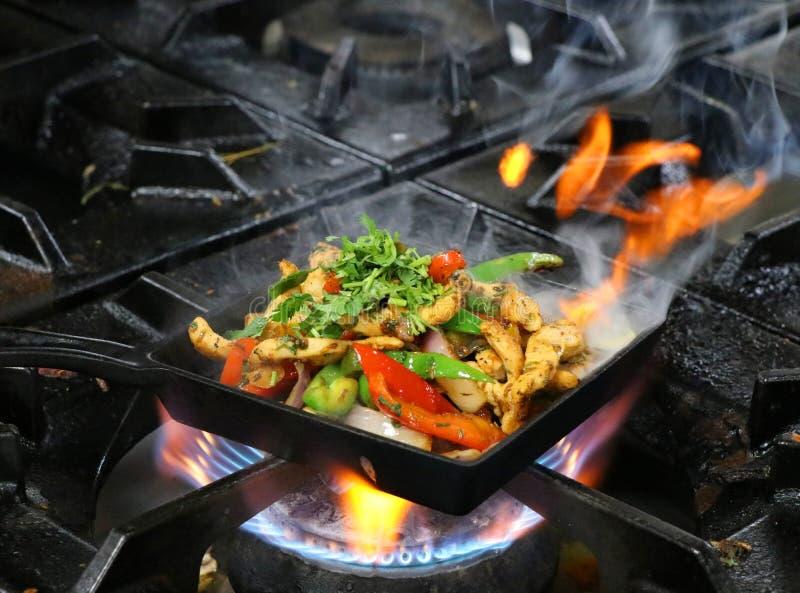 Fajitas mexicains de poulet sur grésiller le plat avec le feu et la fumée images libres de droits