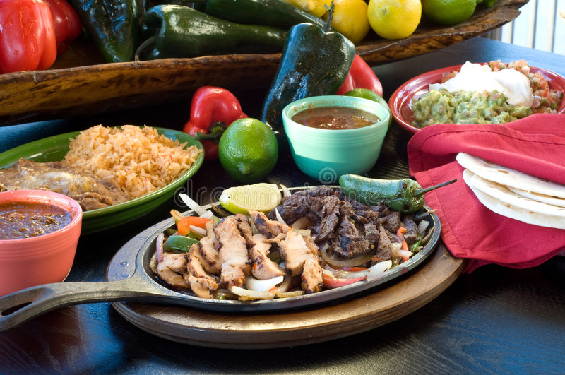 Fajitas - Mexican Food. Fajitas on a skillet with fresh fruit and vegetables in background stock photo