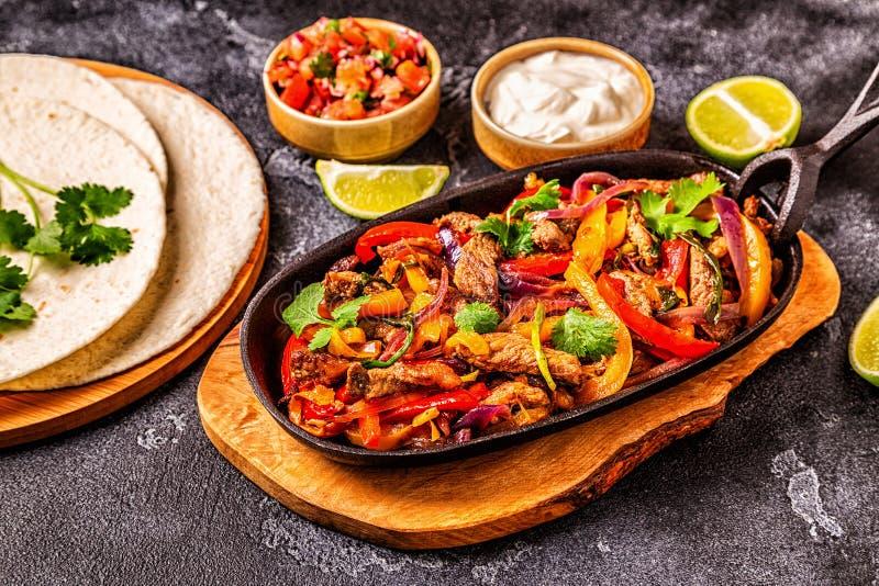 FAJITAS z barwionym pieprzem i cebulami słuzyć z tortillas, obraz stock