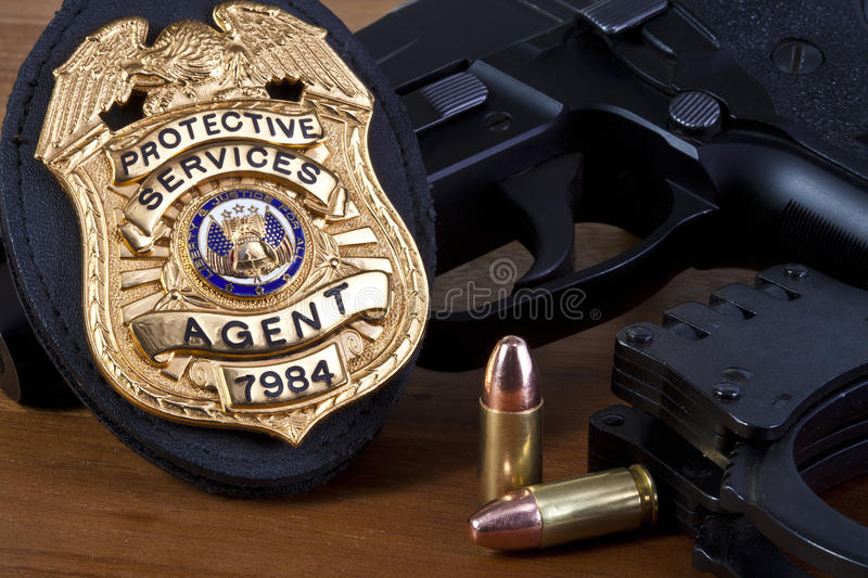 Fake badge made by photographer with handgun, and bullets on wood. stock photos