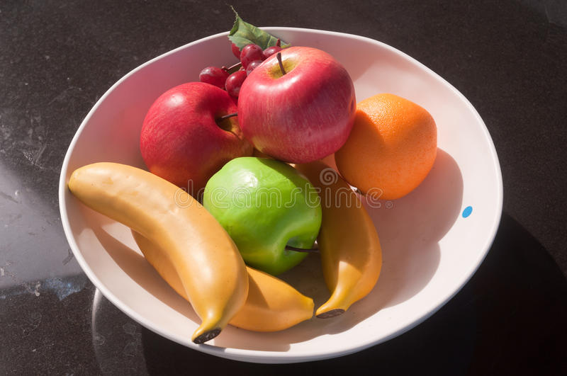 Fake Fruits. Various toy fruits in white plate black on black marble background royalty free stock photos