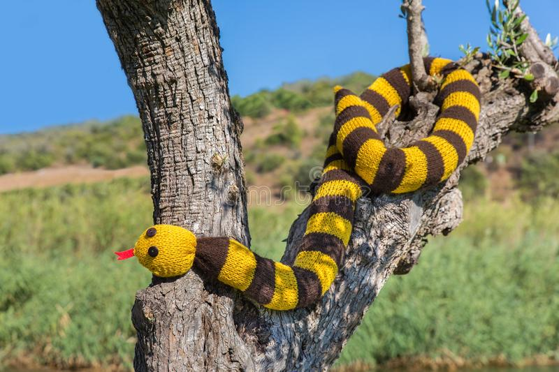 Fake knitted snake hangs in tree trunk stock photography