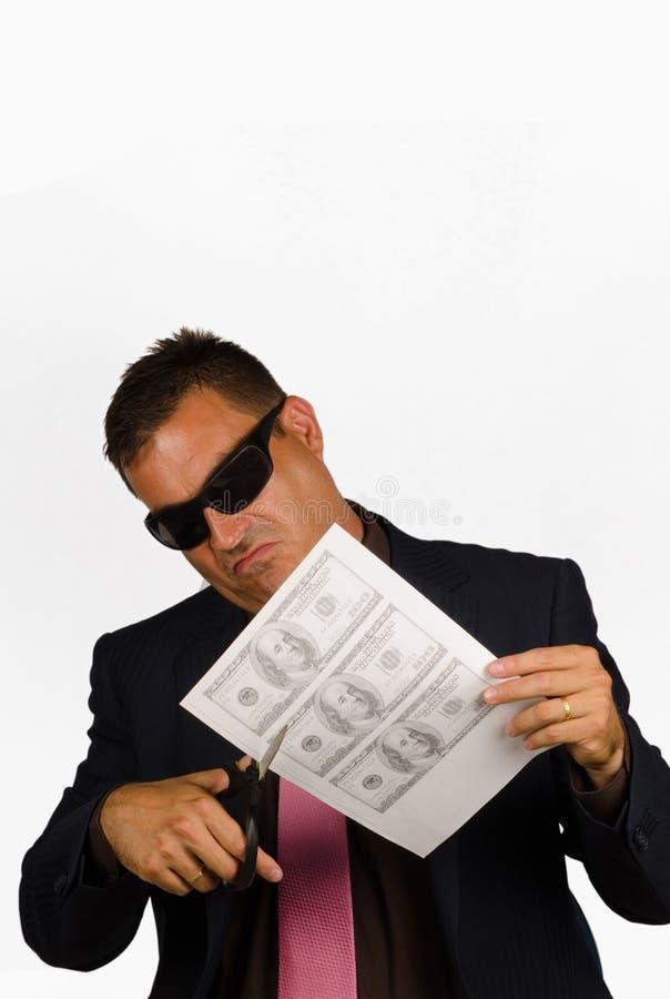Fake money. Guy cutting out fake dollar bills, a concept stock photos