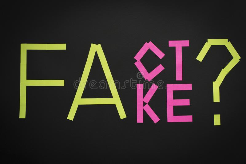Fake News concept. The inscription FACT and FAKE on a black background.  royalty free stock photo