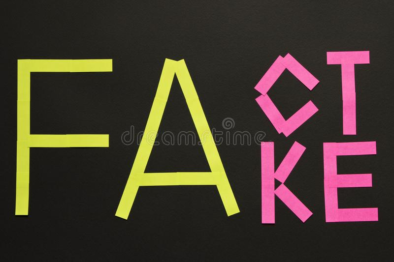 Fake News concept. The inscription FACT and FAKE on a black background.  stock photos