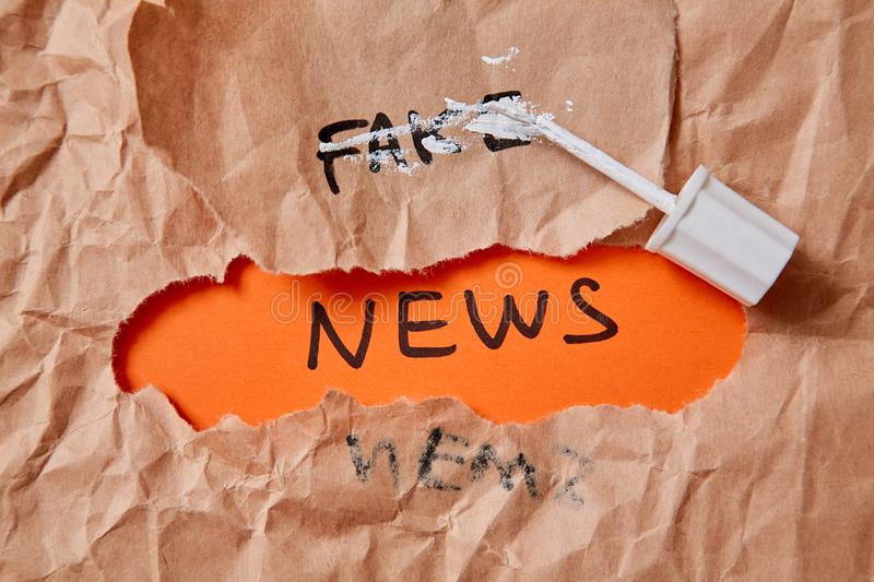 Fake news, disinformation or false information and propaganda concept. Crumpled paper,inscription and corrector royalty free stock images