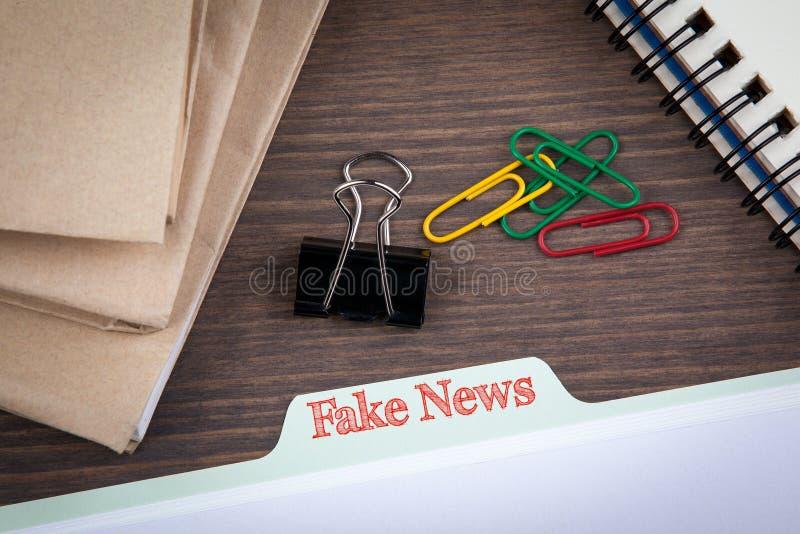 Fake News Infomation concept.Folder Register on a dark wooden desk.  royalty free stock photos