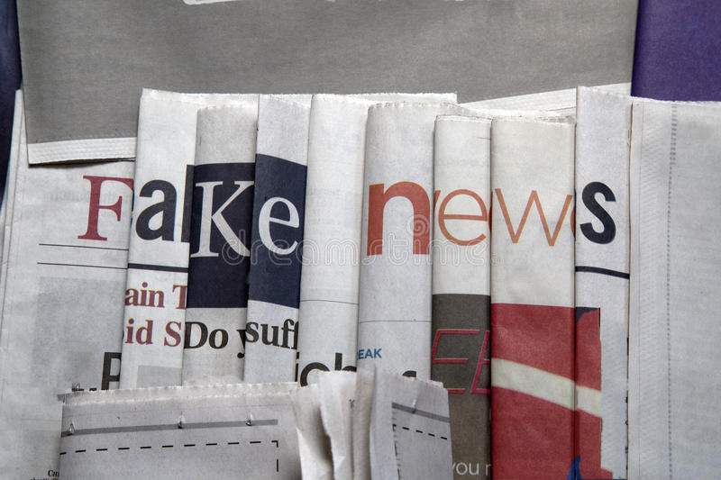 Fake news on newspapers background. Newspaper arranged to display `fake news