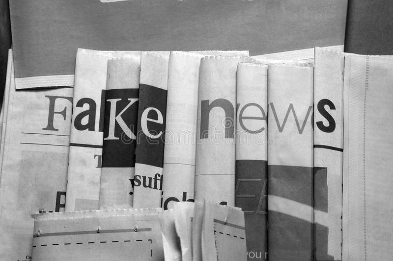 Fake news on newspapers black and white background. Newspaper arranged to display `fake news stock photography