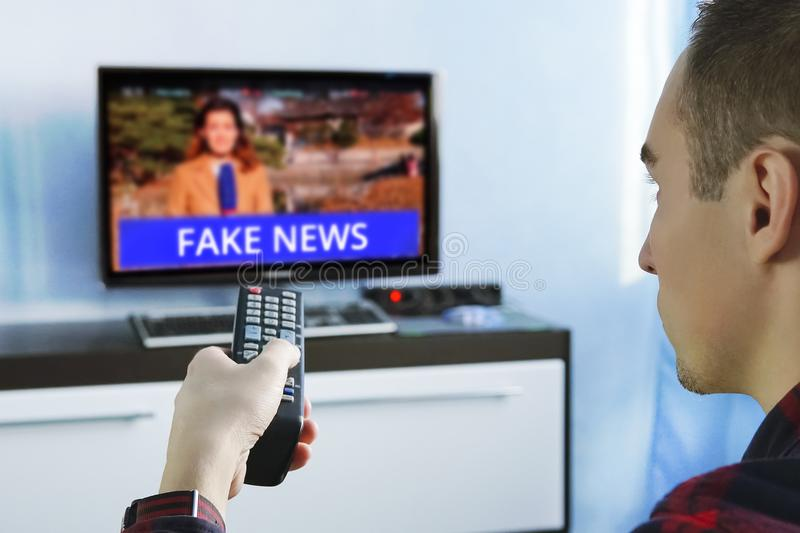 Fake News Propaganda HOAX Political TV Internet Social. Young man watching the fake news report on TV at home. Agitation and propaganda in the modern royalty free stock images