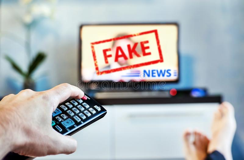 Fake News Propaganda HOAX Political TV Internet Social. young man watching the fake news report on TV at home. Agitation. And propaganda in the modern stock images