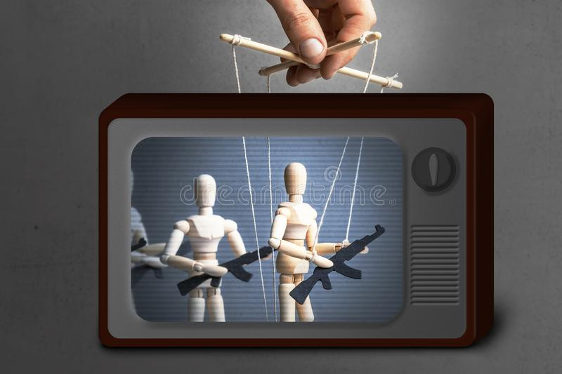 Fake News on TV. Concept of war. People with weapons, armed protest, terrorists. The puppeteer controls the doll with gun royalty free stock photos