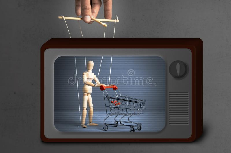Fake News on TV. Control over the behavior of the buyer. Man with shopping trolley from the supermarket like doll by puppeteer. royalty free stock photos