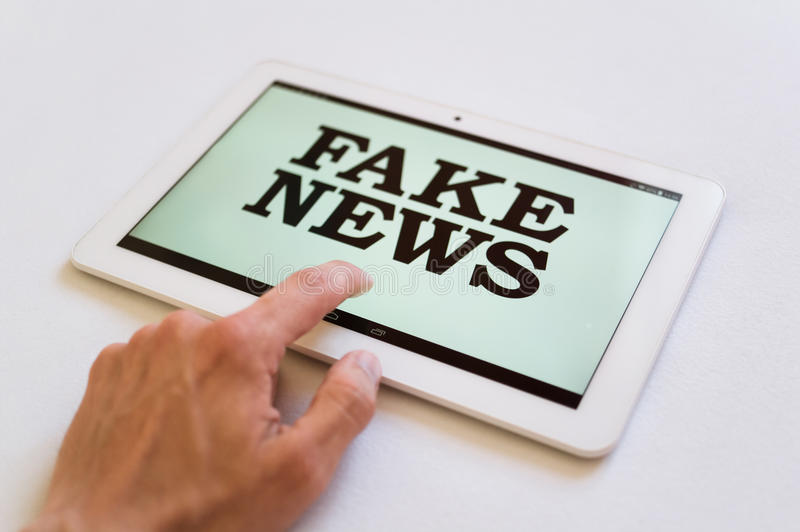 Fake News. User of digital device reads false information hoax, disinformation, propaganda. Misleading and brainwashing of reader stock photography