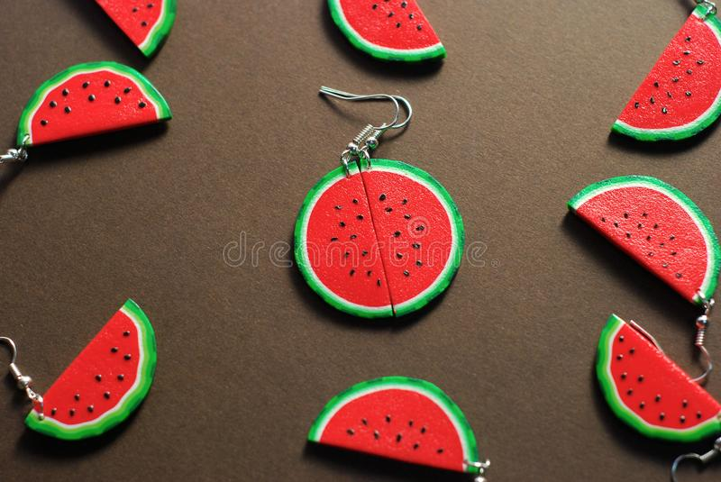 Fake Plastic Fruit Model. Fake Sliced Watermelon Model. Earrings made from Polymer Clay. Brown Background. royalty free stock photo