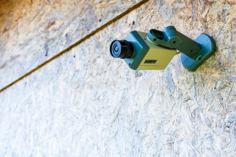 Fake security camera placed on a wooden OSB oriented strand board in sub-urban neighborhood. Concept for private home, security stock images