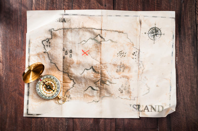 Fake vintage old broken map on wooden desk with compass. Pirates treasure map stock photography
