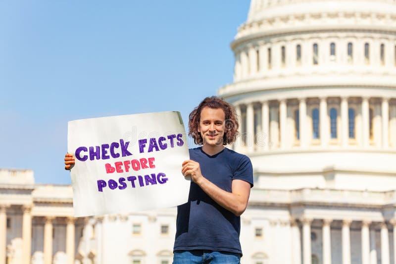 Fakta för kontroll för person som protesterarinnehavtecken, innan att posta royaltyfria bilder