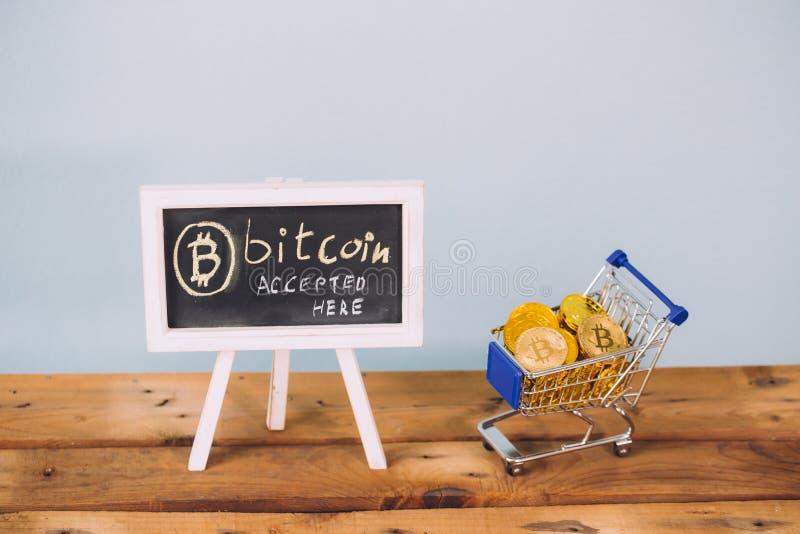 Faktisk valuta Bitcoin accepterade här tecken- och shoppingvagnen mycket av bitcoinmynt på träplattformen över pastellblåttbakgru arkivfoto