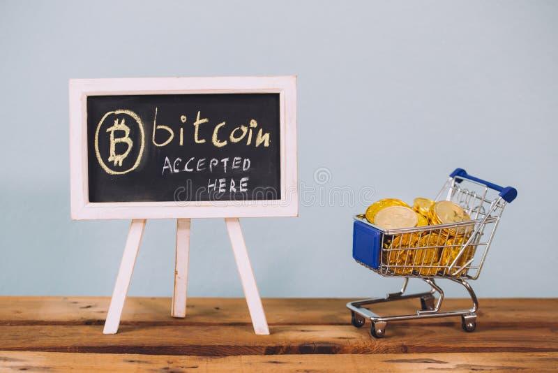 Faktisk valuta Bitcoin accepterade här tecken- och shoppingvagnen mycket av bitcoinmynt på träplattformen arkivbilder