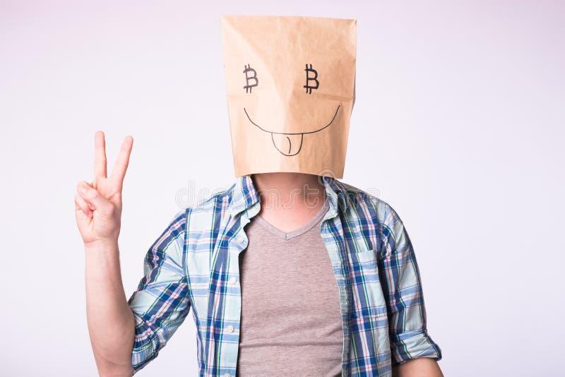 Faktiskt cryptocurrencybegrepp - man med kartongen på hans huvud med bilden av bitcoinsymbolet i stället för ögon royaltyfri bild