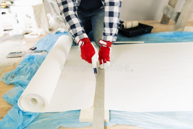 Faktotum arbetare som mäter tapeten för att klippa Hem- renovering- och reparationsbegrepp arkivbilder