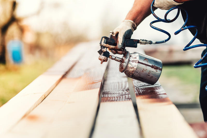faktotum byggnadsarbetaremålning med sprutpistolen på plats Tegelstenar och murbruk arkivbild