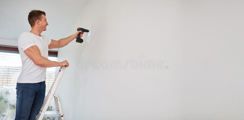 Faktotum med drillborren på väggen på renovering arkivfoto