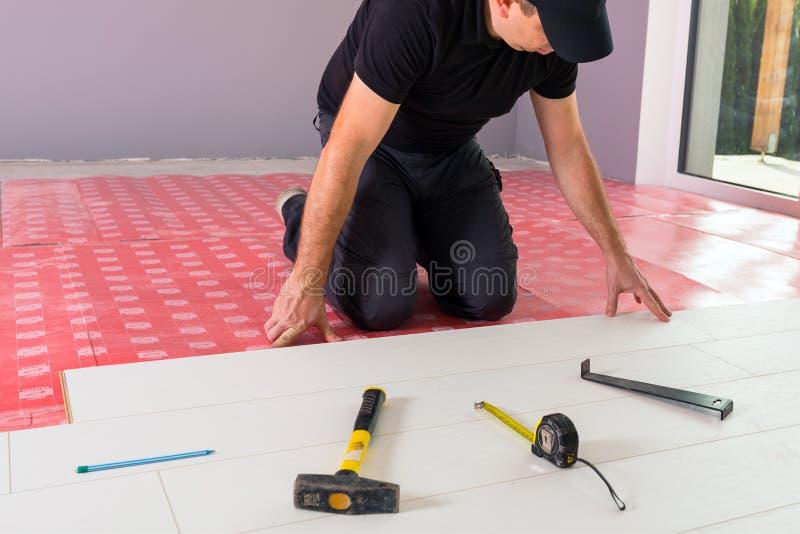 Faktotum som installerar det nya pläterade golvet royaltyfri bild