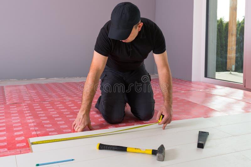 Faktotum som installerar det nya pläterade golvet royaltyfri foto