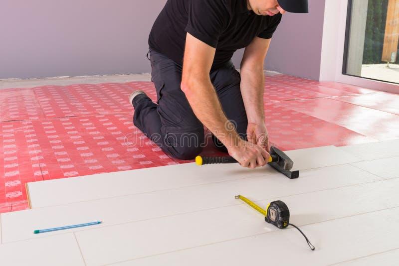 Faktotum som installerar det nya pläterade golvet royaltyfria bilder