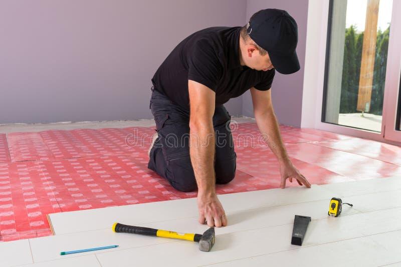 Faktotum som installerar det nya pläterade golvet royaltyfri fotografi