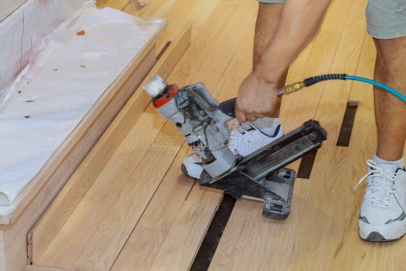Faktotum som installerar huset det i bruk för pneumatisk hammare för trägolv nya royaltyfri fotografi