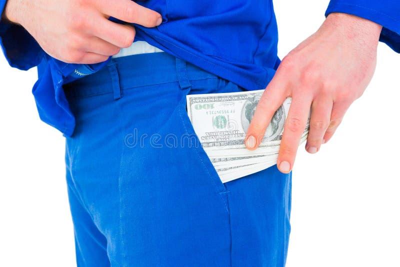 Faktotum som sätter pengar i hans fack royaltyfri fotografi