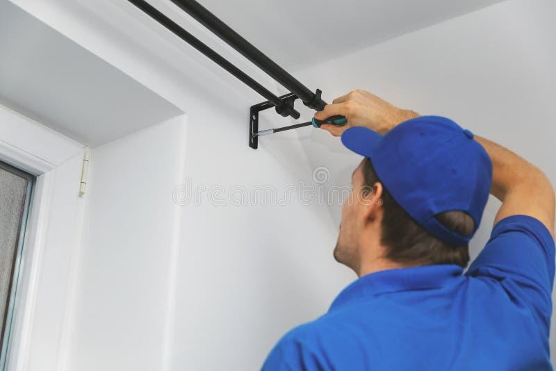 Faktotumservice - arbetare som installerar fönstergardinstången på väggen royaltyfria foton