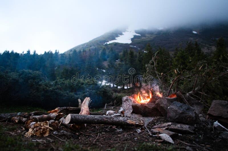 Falò fiammeggiare nel campo durante l'escursione in montagne carpatiche fotografia stock