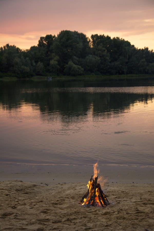 Falò sulla banca del fiume al tramonto fotografia stock