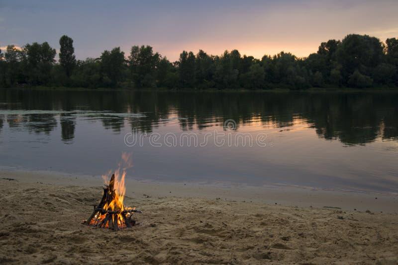 Falò sulla banca del fiume al tramonto immagine stock